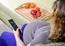 Zwangere vrouw het letten op televisie thuis stock foto's