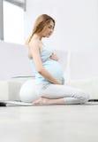 Zwangere vrouw het praktizeren yoga Stock Afbeelding