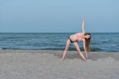 Zwangere vrouw het praktizeren yoga op het strand Zacht avondlicht stock foto