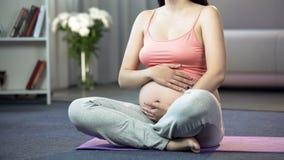 Zwangere vrouw het praktizeren yoga thuis, kalmerend en haar toekomstige baby royalty-vrije stock fotografie