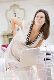 Zwangere vrouw in huisbureau met een pijnlijke rug stock foto