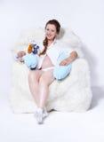 Zwangere vrouw in leunstoel Stock Foto