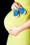 Zwangere vrouw met babyschoenen stock foto's