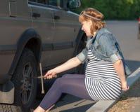 Zwangere Vrouw met de Steun van het Wiel dichtbij Auto stock foto
