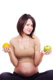 Zwangere vrouw met een appel en een sinaasappel Stock Foto