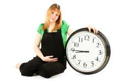 Zwangere vrouw met een klok Stock Afbeeldingen