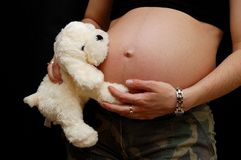 Zwangere vrouw met een stuk speelgoed royalty-vrije stock fotografie