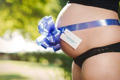 Zwangere vrouw met een teken op haar grote buik stock afbeelding