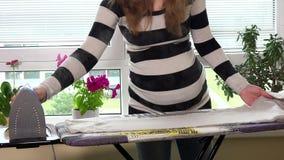 Zwangere vrouw met grote buik en handen die kleren aan boord met damp strijken stock videobeelden