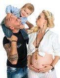 Zwangere vrouw met haar echtgenoot en haar zoon die haar buik kussen royalty-vrije stock afbeeldingen