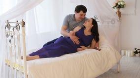 Zwangere vrouw met haar echtgenoot op het bed stock videobeelden