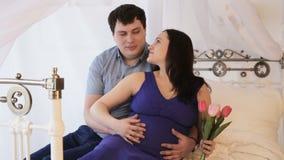 Zwangere vrouw met haar echtgenoot op het bed stock footage