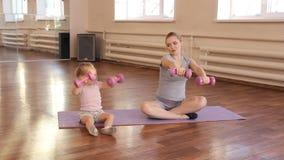 Zwangere vrouw met haar eerste jong geitjedochter die gymnastiek doen stock video