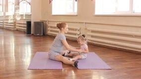 Zwangere vrouw met haar eerste jong geitjedochter die gymnastiek doen stock footage