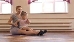 Zwangere vrouw met haar eerste jong geitjedochter die gymnastiek doen stock videobeelden