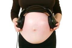 Zwangere vrouw met hoofdtelefoons op maag Royalty-vrije Stock Foto