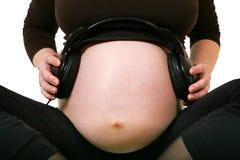 Zwangere vrouw met hoofdtelefoons op maag Royalty-vrije Stock Afbeelding