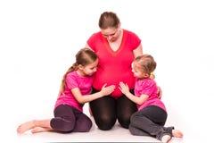 Zwangere vrouw met jonge geitjes geïsoleerd uitoefenen Stock Fotografie