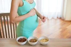 Zwangere vrouw met 3 kommen van noten op de lijst Royalty-vrije Stock Afbeelding