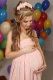 Zwangere vrouw met lang blond haar in elegante kleding, met heel wat kleurrijke luchtballons royalty-vrije stock fotografie