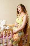 Zwangere vrouw met lang haar met stuk speelgoed Teddybeer in een voederbak thuis. Royalty-vrije Stock Foto