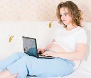 Zwangere vrouw met laptop Stock Foto