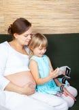 Zwangere vrouw met met dochter en echografierapport royalty-vrije stock afbeelding
