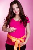 Zwangere vrouw met oranje lint op buik Royalty-vrije Stock Foto's