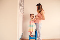 Zwangere vrouw met peuterdochter die pret hebben thuis Stock Afbeelding