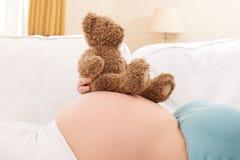 Zwangere Vrouw met Teddy Bear Resting On Belly Royalty-vrije Stock Fotografie