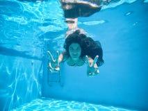 Zwangere vrouw onder het water van een pool stock fotografie