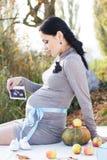 Zwangere vrouw op de aard, de herfsttijd Royalty-vrije Stock Afbeelding