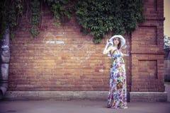 Zwangere vrouw op de achtergrond van een oud huis Stock Afbeelding