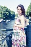 Zwangere vrouw op een brug op een de zomerdag Royalty-vrije Stock Foto's