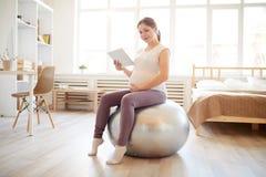 Zwangere vrouw op geschiktheidsbal stock foto