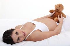 Zwangere vrouw op haar bed royalty-vrije stock foto's