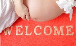 Zwangere vrouw op het wellcome-tapijt Stock Afbeeldingen