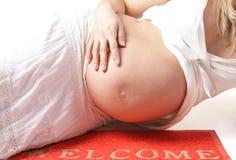 Zwangere vrouw op het wellcome-tapijt Stock Fotografie