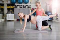 Zwangere vrouw opleiding met persoonlijk bus het uitrekken zich lichaam stock foto