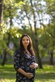 Zwangere vrouw in park Stock Foto