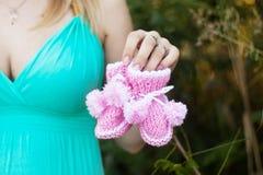 Zwangere vrouw in toevallig met twee soorten sokken Stock Foto's
