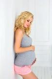 Zwangere vrouw wat betreft haar buik met handen Stock Fotografie