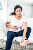 Zwangere vrouw wat betreft voeten terwijl het houden van buik Stock Foto's