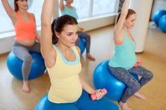 Zwangere vrouwen die met oefeningsballen opleiden in gymnastiek stock afbeeldingen