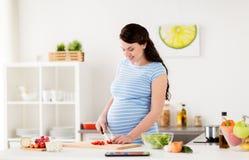 Zwangere vrouwen kokende groenten thuis stock fotografie