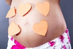 Zwangere vrouwen met schrijfpapier op haar buik Royalty-vrije Stock Afbeelding