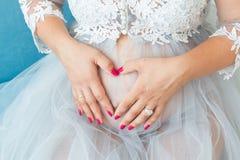 Zwangere vrouwenbuik, de vorm van het zwangerschapshart, liefdeteken stock foto