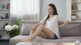 Zwangere vrouwenzitting op bank die lager rug, rugpijn tijdens zwangerschap wrijven stock videobeelden