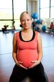 Zwangere vrouwenzitting op de buik van de balholding. stock fotografie