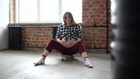 Zwangere vrouwenzitting op een skateboard stock videobeelden